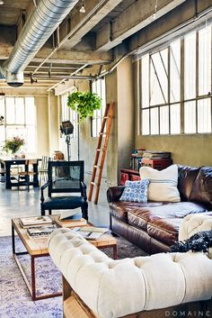 Open floor plan loft apartment with leather couch, ladder, wooden coffee table.
