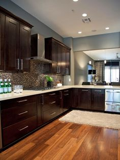 Perfect color scheme!!   Walnut floors with dark espresso cabinetry, quartz counter tops and glass and metal back splash