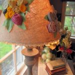 Denise from The Painted Home first wrapped her lampshade with burlap and then adorned it with clusters of fabric flowers.