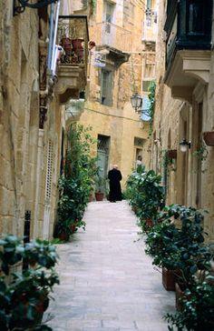 A priest walks a narrow laneway in historic Vittoriosa. Malta