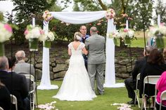bride and groom exchanging vows under arch