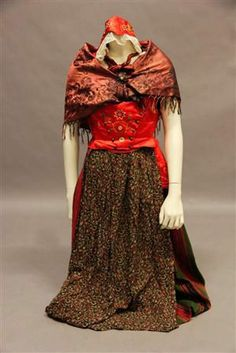 Folkdräkt of StoraTuna in Dalarna, consisting of wide striped skirt, bodice in red silk, apron of pattern woven silk, cap in embroidered silk with lace and silver brooch