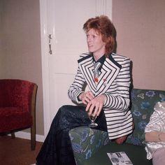 David Bowie, icono de estilo.Otra prenda clave en la gran historia de los looks de David Bowie es esta americana de rayas horizontales y solapas enormes –y de la que Riccardo Tisci propuso una revisión para Givenchy la temporada pasada para gozo absoluto de Courtney Love, que la llevó puesta en varias ocasiones–. Esta imagen se tomó en 1973, un año en el que Bowie era Ziggy y también disfrutaba cambiando sus ajustadísimos monos por pantalones amplísimos y corbatas tamaño XXL.