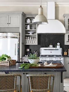 White retro appliances, dark soapstone counters and backsplashes, as well as ash cabinetry painted a muted gray-green (Paris Gray by Annie Sloan Chalk Paint) from Country Living.