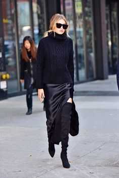 Gigi Hadid in a black chunky knit sweater, side split satin skirt, and over the knee boots