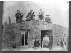Anderson sod house, Logan County, Kansas This photograph shows three men with musical instruments and one man with a rifle on the roof of the Anderson sod house in Logan County, Kansas. Isabel, Matilda and Pete are posed in front of the house. Date: Between 1885 and 1890