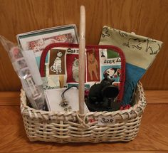 Cat-themed basket includes a kitchen towel, hot pad, stationery, nail file, necklace and a cute statue of a kitty checking things out in the mirror!