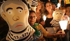 Anti-government demonstrators hold an inflatable doll in the likeness of of Brazil's former President Luiz Inacio Lula da Silva in prison stripes, during protest outside the headquarters of the the Federal Court of Accounts in Brasilia, Brazil, Wednesday, Oct. 7, 2015.