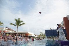 We feel that any bouquet toss should be a toss into the pool! A bride shares a fun moment with guests at Breathless Punta Cana.