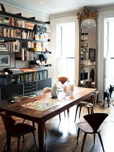 Black Vitsoe shelves, brown wood furniture, white walls and ceramics, big mirror | MilK - Le magazine de mode enfant