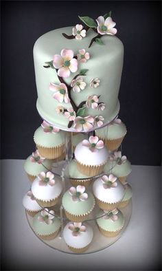 DOGWOOD WEDDING TOWER : Dogwood Cutting Cake with co-ordinating cupcakes in white & hint of apple green colours, topped with a single Dogwood Bloom    Cutting Cake   (Double depth)  From £75    Cupcakes £4.25 each