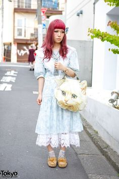 Aibon, a Harajuku girl with romantic vintage style. She has purple hair with bangs and a flower hair accessory. She is wearing a light blue vintage dress from Gunne Sax over a lace slip. Her cat face bag is from the Japanese fashion brand Ahcahcum Muchacha and her moccasins are Minnetonka. Accessories – some from Justin Davis – include an oversized tassel necklace, a watch, pink ring and lace nail art. Aibon mentioned that her favorite labels are Ahcahcum Muchacha and MELANTRICK HEMLIGHET.