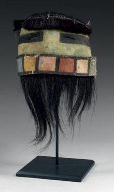 Masque facial demi-circulaire de Kachina ANG-AKCHINA, Kachina HOPI, Arizona, USA Circa 1890-1900 H: Hors crins: 13cm x L: 16,5cm Cuir, crin de chevaux, pigments naturels, coton et tissu de commerce. Demi-masque facial teint de pigments verts aux yeux triangulaires ourlés d'un trait noir, le front ceint d'une frange élaborée en crins de chevaux, le bord inférieur du masque est formé d'une languette de cuir peinte de rectangles de couleurs rouge, jaune, blanche, bleu, ocre et vert…