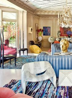Light blue leather sofas, gold head bust, and a crystal chandelier