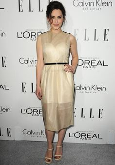 Emilia Clarke  con un vestido midi en crema con transparencias más cinturón y detalles en los hombros en negro de Calvin Klein Collection.