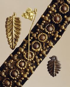 Selection of Medieval dress ornaments. In the centre is a detail of a leather belt which was found in two pieces and with traces of silk covering. It has three rows of brass mounts and a smaller fragment with pierced rectangular mount. On the right is a dress ornament in the shape of a leaf of tinned iron with a suspension ring. On the left is an embossed leaf probably a dress ornament or belt fitting with part of the attachment loop missing. Next is a pin linked to an embossed acanthus…