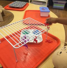 Breeyn spent time in a toddler classroom in Lancaster, PA yesterday and saw this great idea in a two-year-old classroom! The teacher's addition of this simple shelf riser during her welcome activities encouraged the children to refine their fine motor skills while at the same time expanding on their persistence and problem solving skills. Using the materials in their classroom in a new way provides many ways to build upon this activity.