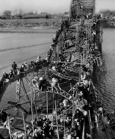 Max Densfor, Refugees from Pyongyang, North Korea, crawl perilously over shattered girders of the city's bridge, as they flee south to escape the advance of Communist troops, 1950