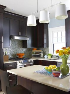 Modern Kitchen  The sleek kitchen is where modern style really shines in the Victorian home. The streamlined look of the space is accented with a light blue tile backsplash and the simple white light fixture over the island. Pops of bright colors add freshness.