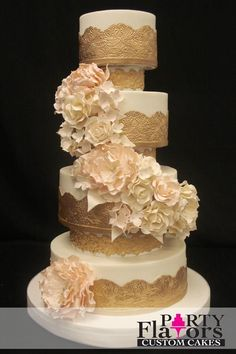 This stunning wedding cake is reaching new heights, thanks to the embellished spacers between each layer. Embossed gold appliques and a cascade of blooming sugar flowers make this cake truly outstanding.