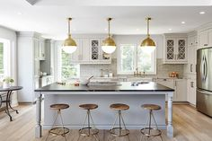 Exquisitely appointed kitchen boasts three Hicks Pendants hung over a black marble countertop accenting a gray island with turned legs seating four Arteriors Wyndham Stools on slightly stained wood floors. Outdoor Kitchen Countertops, Outdoor Kitchen Bars, Outdoor Kitchen Design, Open Kitchen, Kitchen Dining, Kitchen Decor, Kitchen Ideas, Gold Kitchen, Kitchen Stools