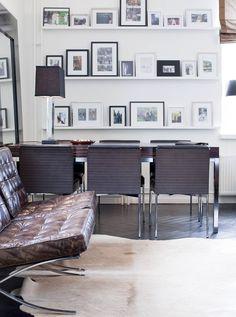 Zebranolevyinen ruokapöytä on Jaanan suunnittelema. Nahkaiset tuolit on hankittu Milanon messuilta. Kuvaseinällä on kooste muistorikkaista yhteisistä hetkistä maailmalla. Taulu-hyllyt ovat Frimodig-kehyksestä.