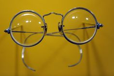 """John Lennon's round """"Windsor"""" glasses, displayed at the Rock and Roll Hall of Fame in New York City."""
