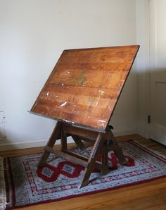 We found an antique drafting table like this one at a local antique store.  My hubber couldn't wait to get his hands on it!  Stripped, restained and it's now part of his daily life in his office.
