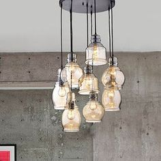This Mariana Cognac Glass Cluster Pendant in Antique Black Finish features eight lights each covered with a cognac finish shade. The lights hang at separate lengths supported from an antique black iro...