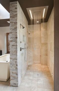 Large tub in the center of the room with a walk-through oversized shower behind the tub on the other side of the wall.