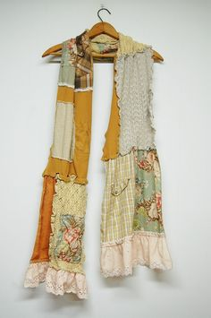 This boho patchwork scarf is constructed of recycled fabrics in soft neutral colors. It is trimmed at the ends with a shabby cotton ruffle and adorned on both sides with tattered patches. The raw edges and exposed stitching lend to the unique tattered design. The scarf measures approximately 13.5 wide and 86 long. Care: Machine wash. Tumble dry low.  SATISFACTION GUARANTEED If for any reason you are not satisfied with your purchase you have 14 days from receipt of item to return it (not…
