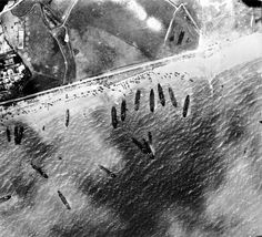 """L'ouest vers Courseulles sur Mer. Les """"dunes"""" entre Bernières et Courseulles, la ligne blanche parallèle à la côte est la voie ferrée de la ligne: Caen-Courseulles sur Mer. Vous remarquez que tous les engins tournent à gauche, en contournant un épi, pour gagner la sortie par la rue des Ormes, car en face des navires la voie est inaccessible : digue en béton puis dunes de sable, voie ferrée et pire en contre bas une prairie humide impraticable."""