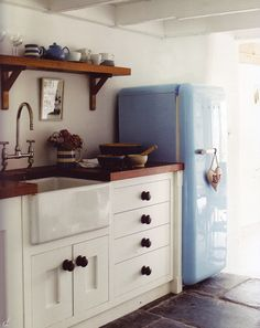 Wooden countertop, white walls, blue retro fridge, ceiling detail, exposed beams