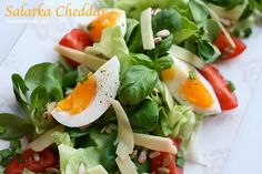 Salad with egg, tomato, cheddar cheese and sunflower seeds.  The recipe for a tasty salad with cheese and eggs.