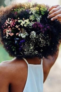 Afro Bloomin' hairstyles with colorful flowers in afros. | essence.com
