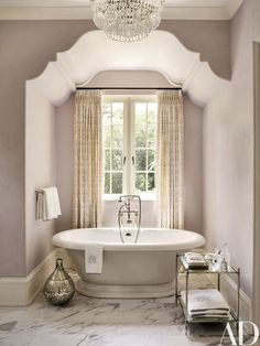 The master bath, painted in Benjamin Moore's Violet Pearl, features Waterworks tub fittings | archdigest.com