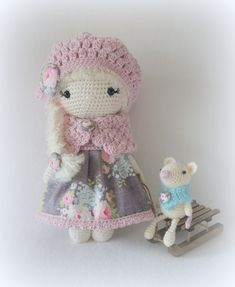Crochet doll with a pink hat and floral fabric dress with her tiny amigurumi mouse friend by smoozlycrochet.
