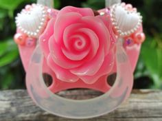 A special paci for a special princess.  Base pacifier has an orthodontic cherry made of silicone and is BPA free. Designed to suit 0-6 months.   Embellished with a pink rose, white pearls hearts and a sprinkle of pearls and diamantes, this one of a kind paci will bring the sunshine to your da...