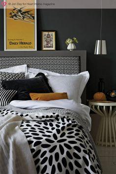 Bogactwo etnicznych wzorów i faktur w tej sypialni łagodzi grafitowa gładka ściana. Na jej tle lśni nowoczesny chromowany klosz wiszącej lampy. Jest ona alternatywą dla lampy stołowej.
