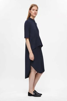 This shirt style dress is made from soft wool with a crepe textured quality. Designed with a layered skirt that has folds softly at the front and is longer at the back, it has a neat collar, concealed front buttons and subtle in-seam pockets.