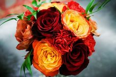 This bouquet of deep orange and red roses is so stunning for a fall wedding.
