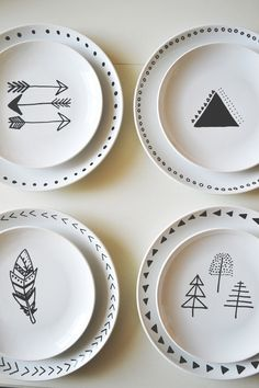 paint solid white plates with black or dark grey arrows, feathers, and trees -- hang on a wall