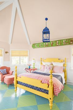 Bedroom SuiteWhen it came to decorating the kids' area, which includes both Theo and Amelia's bedrooms, bathrooms, and a playroom, Alison chose to unify the spaces with a turquoise-and-lime painted floor that runs throughout. The peach walls of Amelia's bedroom complement a yellow bed (ethanallen.com), marigold window treatments (pindler.com), an orange-red side table, a coral chair, and pink-and-red-and-navy linens. The blue lantern (straydogdesigns.com) features a sweet scalloped trim.