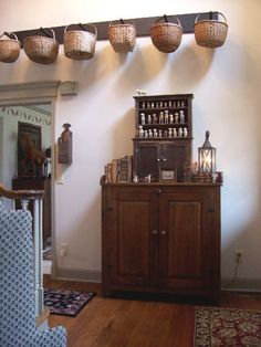 ANTIQUE CABINETS WITH A PUTZ SHEEP COLLECTION AND A PEG RACK WITH ANTIQUE BASKETS ABOVE.
