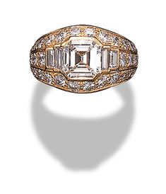 A DIAMOND COCKTAIL RING, BY CARTIER   Bezel-set with a rectangular-cut diamond flanked by baguette-cut diamonds in a circular-cut diamond half-hoop surround, mounted in 18K gold, size 6½, with French assay mark, in a Cartier red leather case  Signed Cartier, no. 654669   2.00 carats