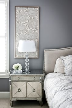Framed wallpaper above night stands? Coordinate by wallpapering closet?love the dark gray wall color, light gray textured headboard with beading, the clean look of the down comforter, the glass end table and the framed wallpaper as art work. Home Bedroom, Bedroom Decor, Bedroom Furniture, Gray Bedroom, Master Bedrooms, Mirror Furniture, Serene Bedroom, Mirror Bedroom, Furniture Ideas