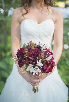 Brides.com: . A deep red bouquet of mums with pops of white and green flowers created by Camp Joy Gardens.