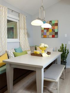 Modern Kitchens from Drew and Jonathan Scott on HGTV The light grey walls, yellow print window treatment and cozy bench seating with pillows next to the table creates a unique, cozy spot for casual meals, homework and family gatherings. Love the homey, comfortable feel!