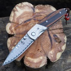 Cocobolo Linerlock Folder  This BucknBear Folding Knife embraces the classic folder with its lines, style and craftsmanship. The ladder Damascus folder features with a hollow grind, an elongated nail clip, and standard blade style. The elegant handle features Cocobolo wood scales, damascus bolsters with mother of pearl thumb rest Includes Lanyard Includes a premium leather sheath.