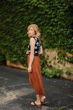 Nice colour combo. Rust orange midi skirt and b&w top. Flat sandals.